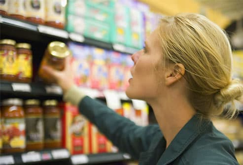 Woman choosing jar from supermarket shelf