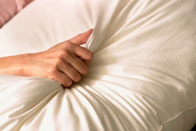 photo of woman clutching pillow