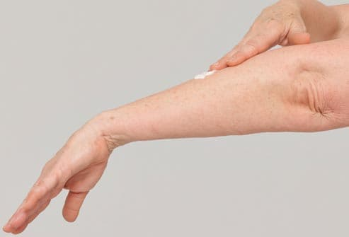 Woman applying cream to forearm