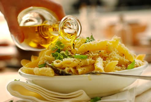Close up on hand pouring oil onto pasta