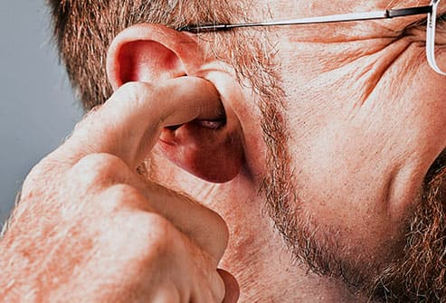 man scratching ear