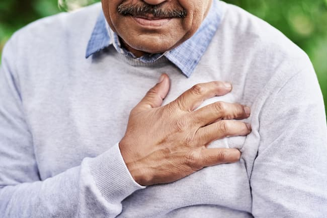 photo of man holding chest