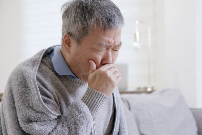 photo of mature man coughing