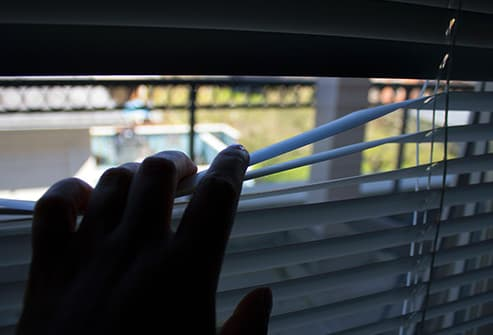 hand pulling down blinds