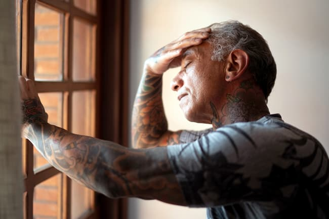 photo of fatigued man standing by window