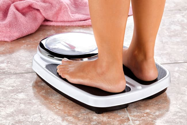 photo of woman standing on weight scale