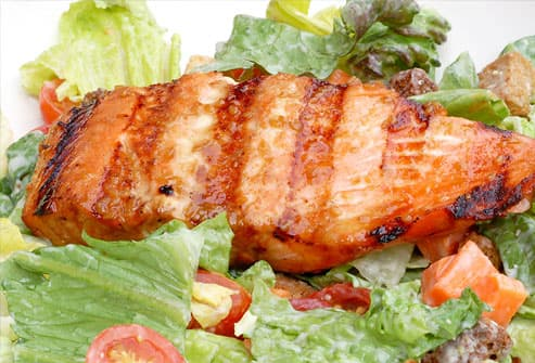 Grilled salmon on a plate of salad