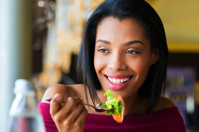 photo of woman eating salad