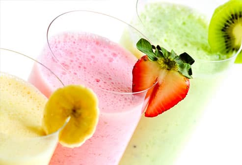 Assorted fruit smoothies on white background