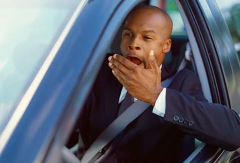 Man yawning while behind the wheel of a car