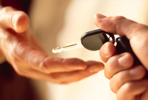 One hand transferring car key to another open hand