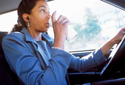 Woman drinking coffee while driving