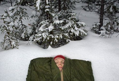 Woman asleep in sleeping bag in snowy landscape