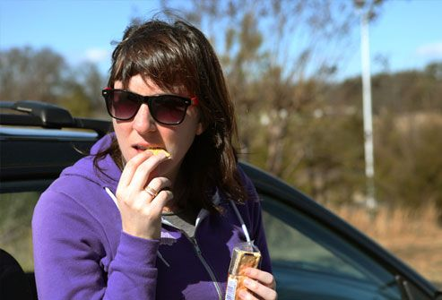 Woman pulled over and snacking on crackers