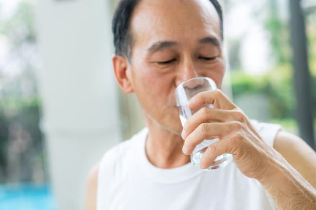 photo of mature man drinking glass of water