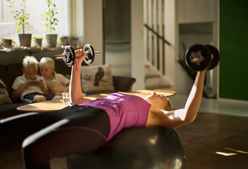 Woman lifting weights in living room