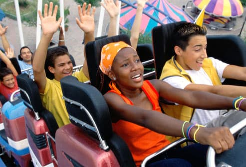 teens riding a roller coaster
