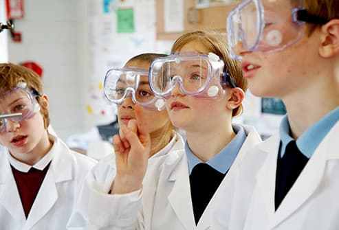 children wearing goggles in science class