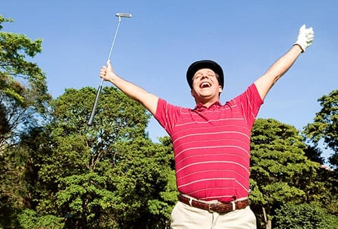 man celebrating on golf course