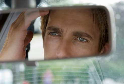 young man looking into rearview mirror