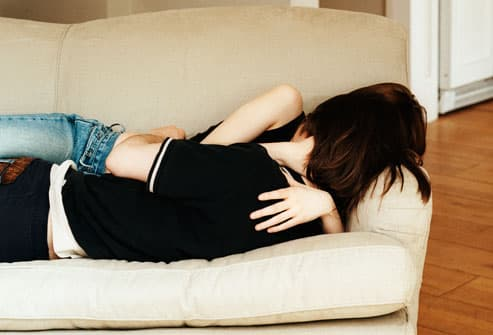 Teenagers Embracing On Couch