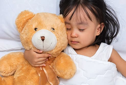 girl sleeping with teddy