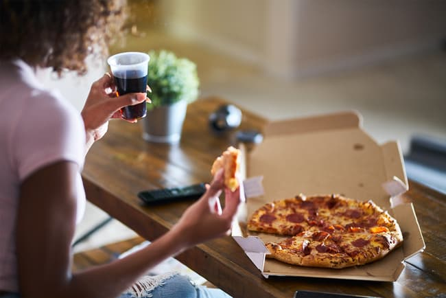 photo of woman eating a pizza