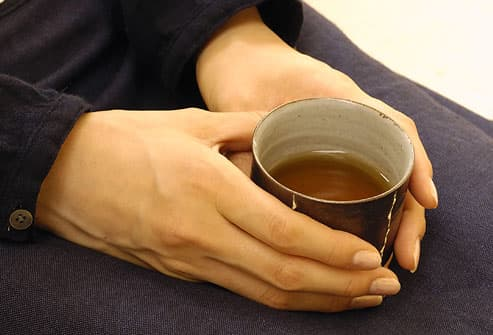 woman holding a cup of black tea