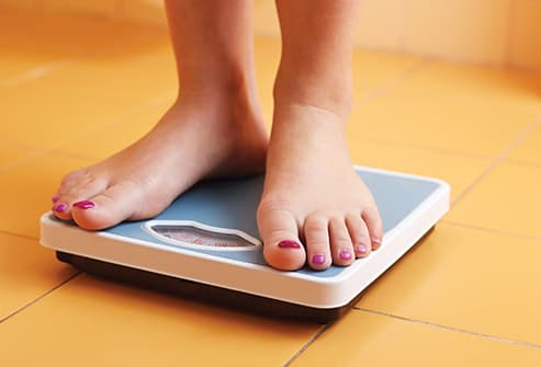 woman on weight scale at home