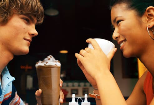 Teen couple having coffee drinks at cafe