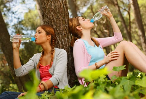 Teen girls breaking from hike to enjoy water