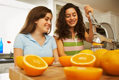 Teen girls juicing fresh oranges in kitchen
