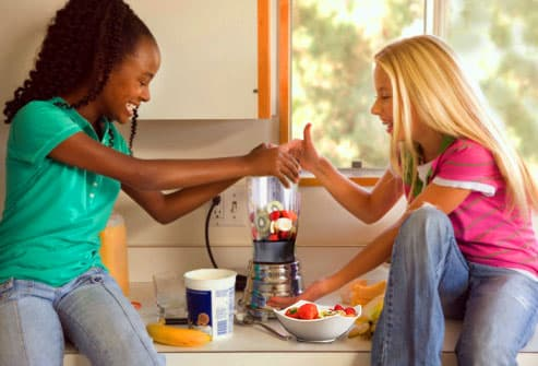 Teen girls making a healthy fruit smoothie