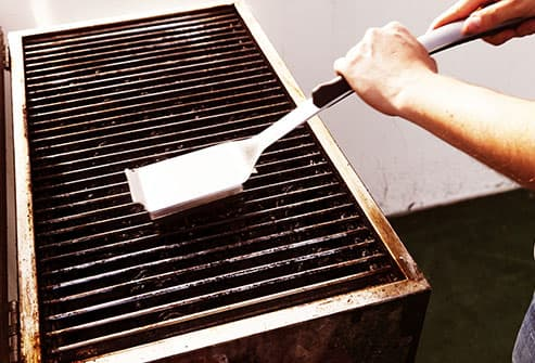 man cleaning grill