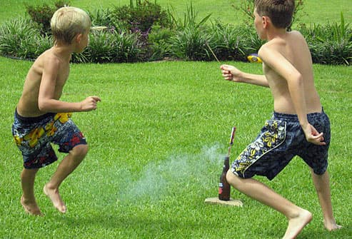 Two boys setting off firecrackers in summer
