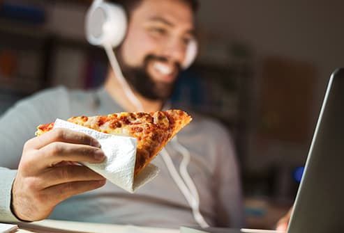 man eating pizza slice
