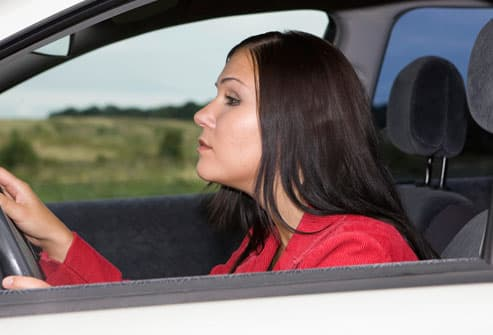 Woman Hunched Over Steering Wheel