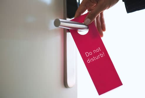 Man Putting Do Not Disturb Sign on Door