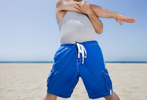Man Doing Stretches on Beach