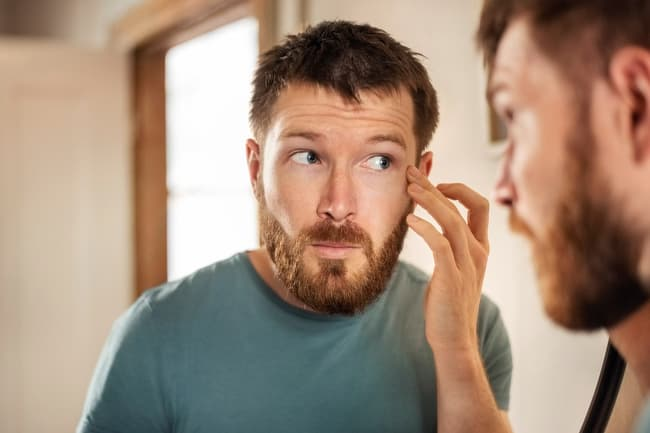 photo of man checking face in mirror