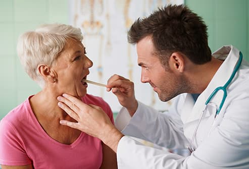 doctor examining throat of senior woman