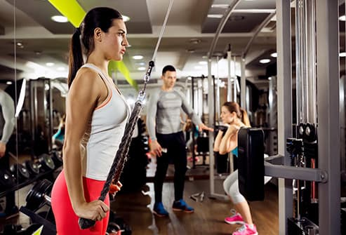 young woman strength training in gym