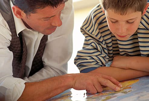 Father and son looking at map