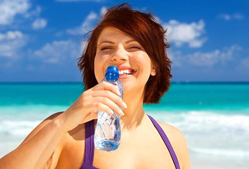 woman on beach with water bottle
