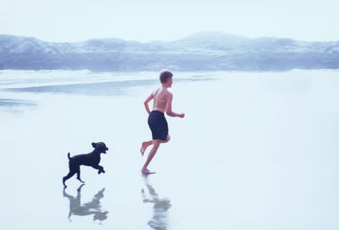Boy and Puppy Running on Beach
