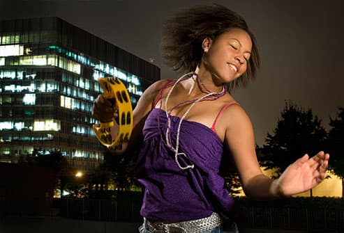 Teen girl dancing with tambourine