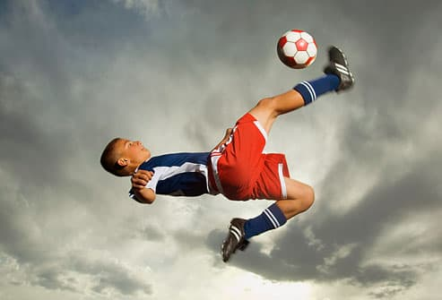 teen kicking soccer ball