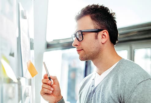 young man studying sticky notes