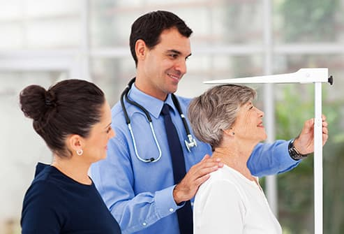 doctor measuring senior height
