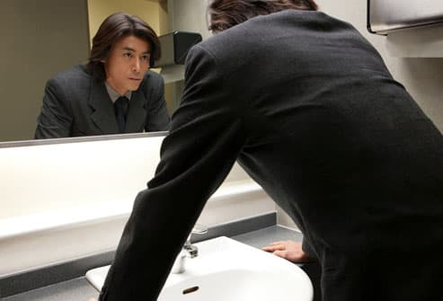 Unhappy man staring at his reflection in a mirror